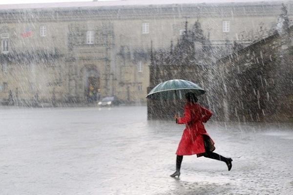 A woman crosses the Obradoiro square during a heavy storm in Santiago de Compostela, Galicia, northwerstern Spain, Nov. 4, 2014.